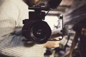 Et videokamera blir festet til et stativ i moderne kontoromgivelser.
